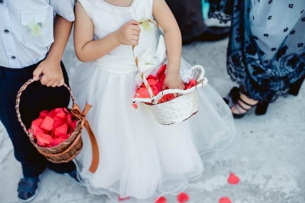 Śliczna chłopiec i dziewczyna w białej sukni i kostiumu z koszykowym miotaniem czerwieni róży płatki przy ślubem