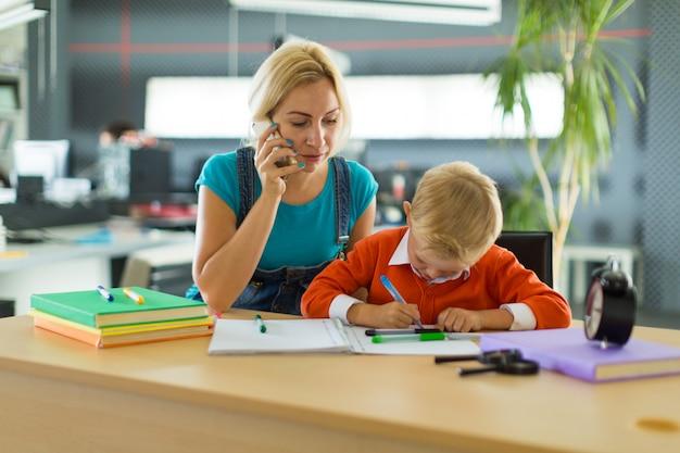 Śliczna chłopiec i kobieta siedzimy przy biurkiem w biurze
