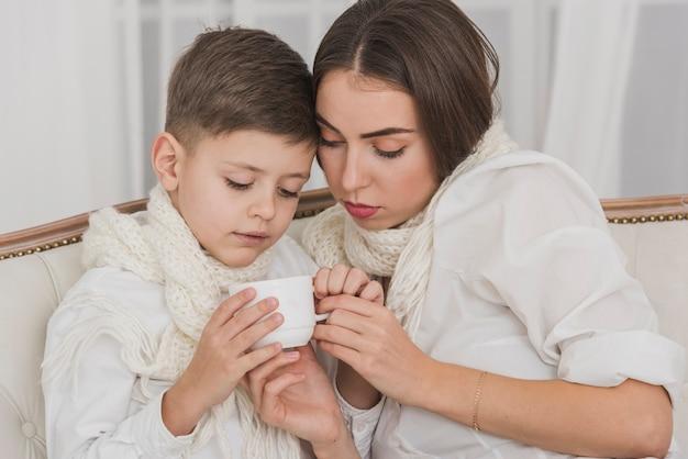 Śliczna chłopiec i matka trzyma filiżankę