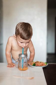 Śliczna chłopiec je makaron i pije sok