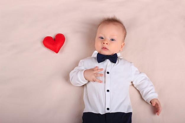 Śliczna chłopiec jest ubranym smokingu i łęku krawat z czerwieni zabawkarskim sercem jako symbol matka dzień z kopii przestrzenią