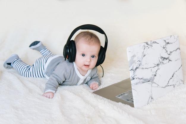 Śliczna chłopiec kłama na jego żołądku w hełmofonach i spojrzeniach w laptopie, selekcyjna ostrość