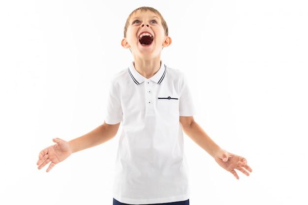 Śliczna chłopiec krzyczy z uderzeniami w białej koszulce z rękami szeroko rozpościerać na białym tle z kopii przestrzenią