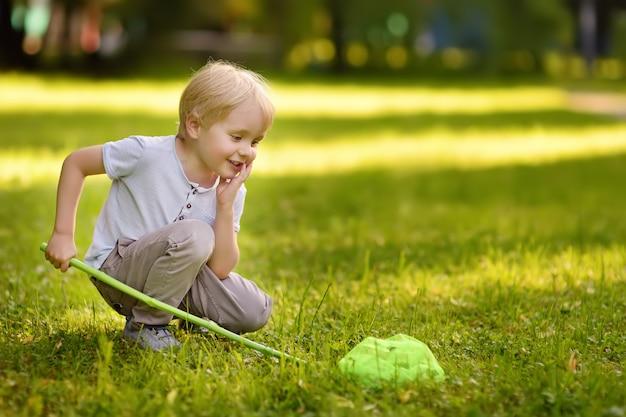 Śliczna chłopiec łapie motyle z miarką na słonecznej łące. młody przyrodnik.