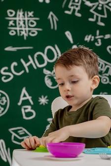 Śliczna chłopiec lejni od plasteliny na stole z blackboard na tle. gotowy do szkoły. edukacja domowa. powrót do szkoły