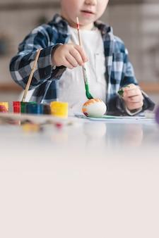 Śliczna chłopiec maluje jajka dla easter