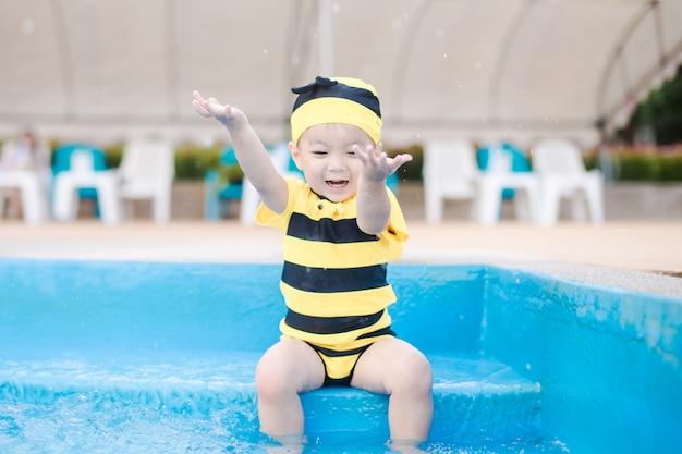 Śliczna chłopiec na żółtym swimsuit bawić się w pięknym błękitnym pływackim basenie