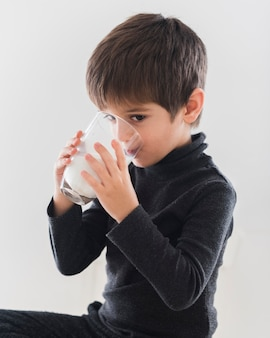 Śliczna chłopiec pije szkło mleko
