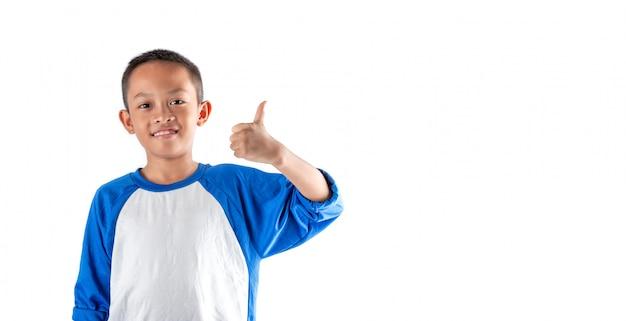 Śliczna chłopiec pokazuje kciuk up z smiley twarzą. cudowny chłopak czuje się szczęśliwy i zrelaksowany. ma dobre zdrowie i cieszy się życiem.