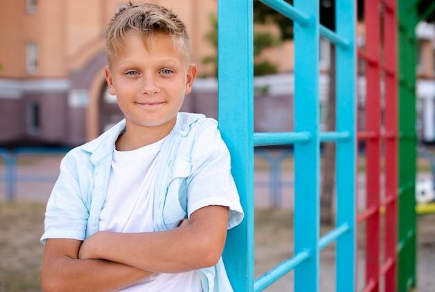 Śliczna chłopiec pozuje dla kamery z jego rękami krzyżować