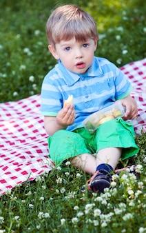 Śliczna chłopiec przy pinkinem w parku