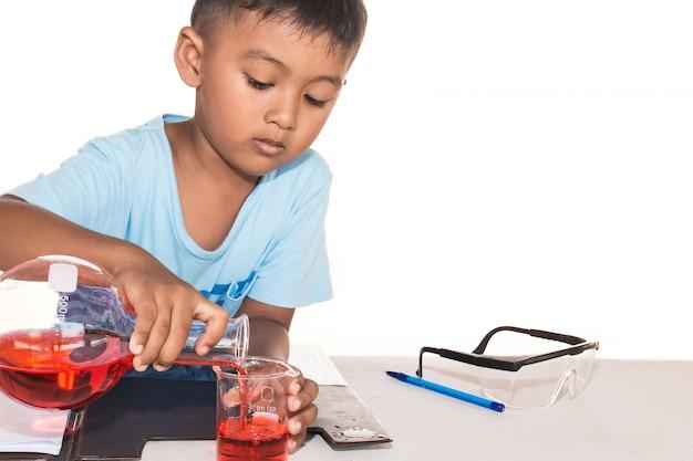 Śliczna chłopiec robi nauka eksperymentowi, nauki edukacja, azjata dzieciaki i nauka eksperymenty na białym tle