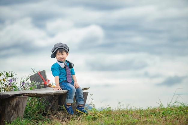 Śliczna chłopiec samotnie plenerowa na górach z chmurą