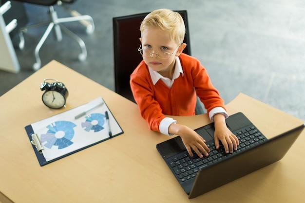 Śliczna chłopiec siedzi przy biurkiem w biurze i używa komputer