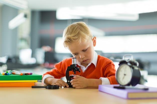 Śliczna chłopiec siedzi przy biurkiem w biurze, trzyma mikroskop