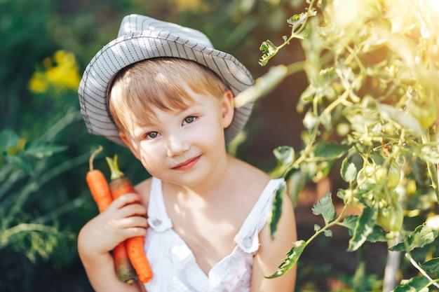 Śliczna chłopiec siedzi wokoło pomidorów ang i kapeluszu w przypadkowych ubraniach ang, patrzeje kamerę, dzieciaka wzorcowy pozować w ogródzie