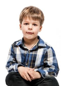 Śliczna chłopiec w przypadkowej kwadrat koszula na bielu