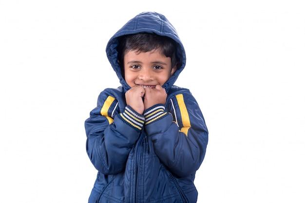 Śliczna chłopiec w zima żakiecie odizolowywającym na białej ścianie