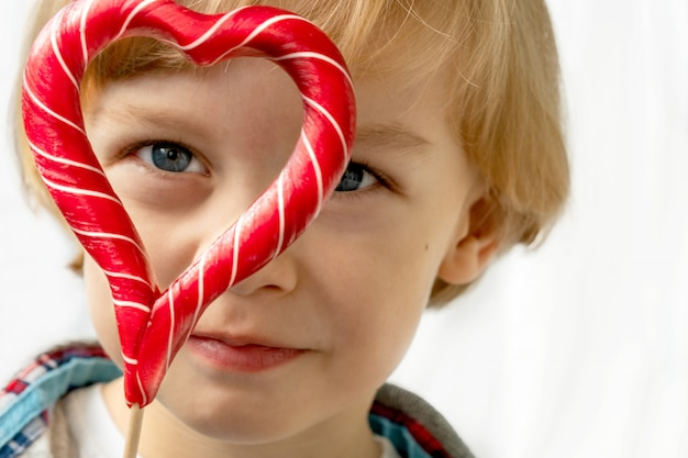 Śliczna chłopiec wewnątrz z cukierków czerwonymi lizakami w kierowym kształcie, biały tło. piękne dziecko je słodycze. walentynki, pojęcie miłości.