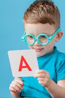 Śliczna chłopiec z listem na tle. dziecko uczy się liter. alfabet