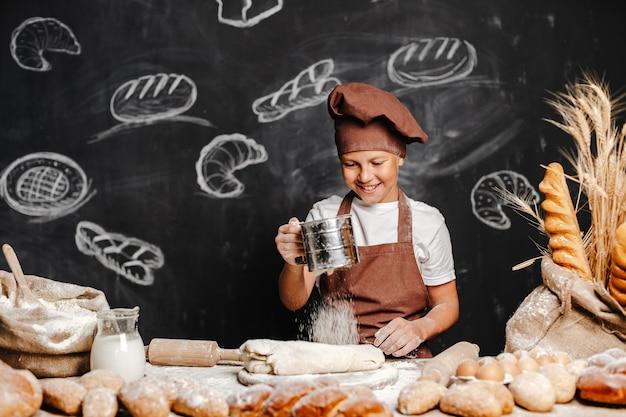 Śliczna chłopiec z szefa kuchni kapeluszu kucharstwem