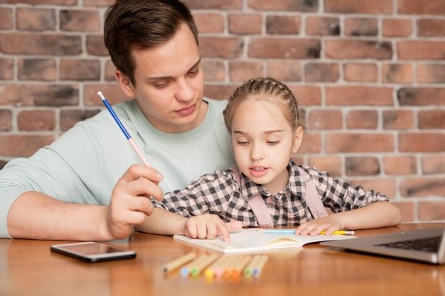 Śliczna, ciekawa córka z zaplecionymi włosami siedząca na kolanach ojca przy stole i opisująca tacie rysowanie podczas wspólnego odrabiania lekcji