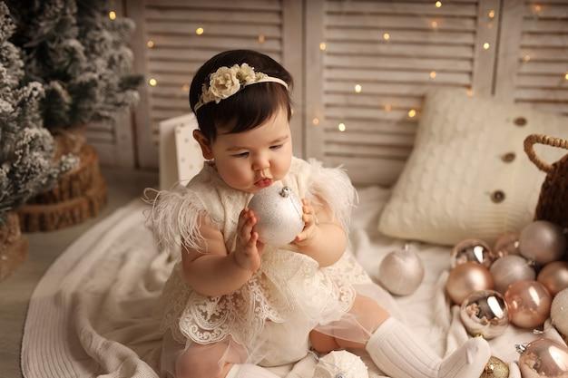 Śliczna ciemnoskóra dziewczyna siedzi na białym dzianinowym kocu i bawi się zabawkami na choinkę
