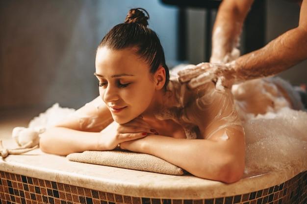 Śliczna, ciemnowłosa kobieta ma relaksujący masaż pianką w tureckiej łaźni tureckiej wellness.