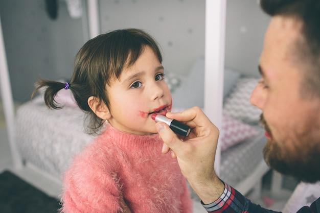 Śliczna córeczka i jej przystojny młody tata bawią się razem w pokoju dziecka. dziewczyna robi tacie makijaż.
