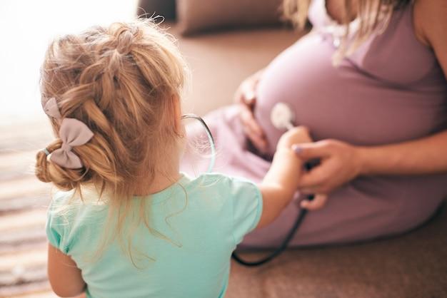 Śliczna córka bawi się w lekarza i sprawdza ciężarną matkę