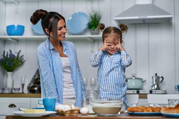 Śliczna córka i jej młoda mama rozkładają ciasto w kuchni na stole