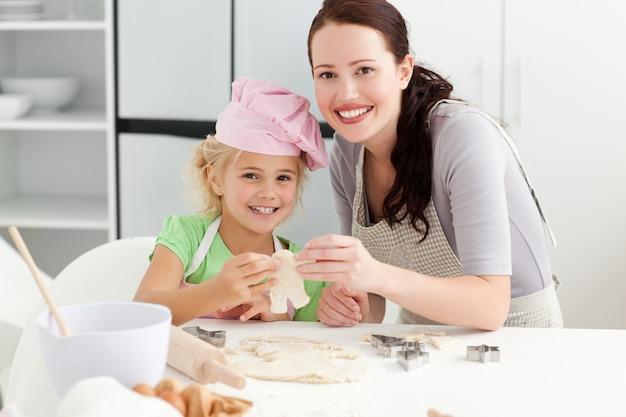 Śliczna córka i matka pokazuje ciastko w formie mężczyzna