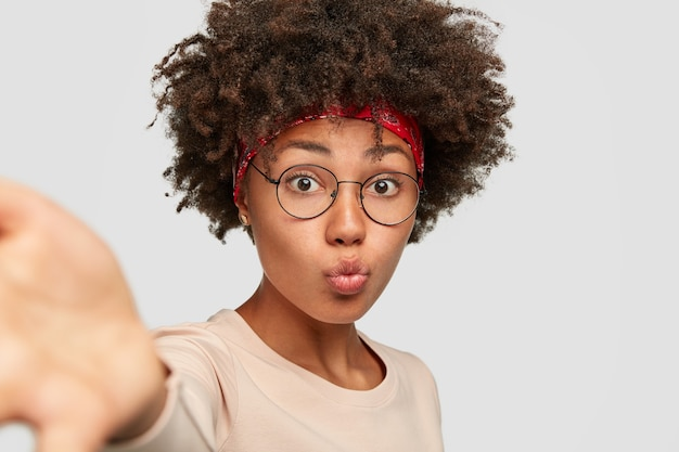 Śliczna czarna oman wydyma usta, gdy robi selfie, wyciąga ręce z przodu, nosi przezroczyste okulary i swobodny sweter