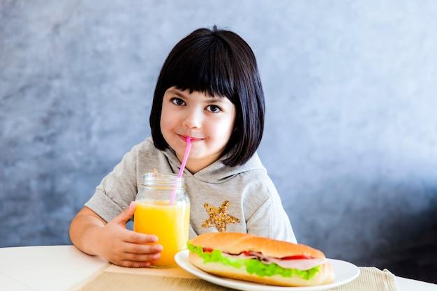 Śliczna czarni włosy mała dziewczynka ma śniadanie i pije sok pomarańczowego