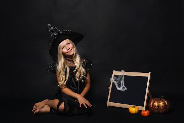 Śliczna czarownica blisko blackboard i bani