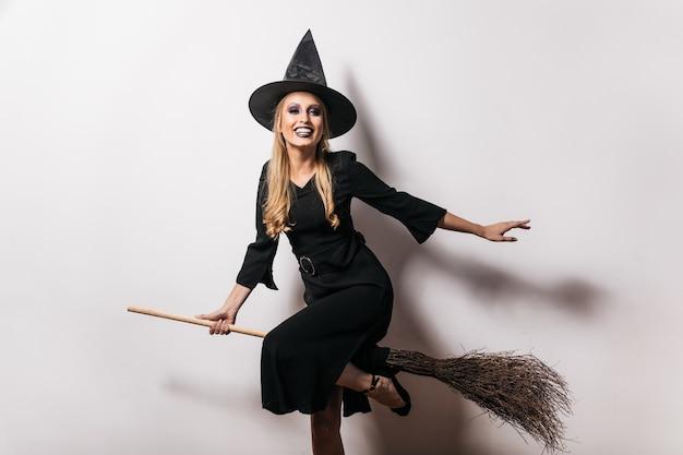 Śliczna czarownica w długiej sukni siedzi na miotle z uśmiechem. beztroska blondynka w stroju karnawałowym ciesząc się halloween.