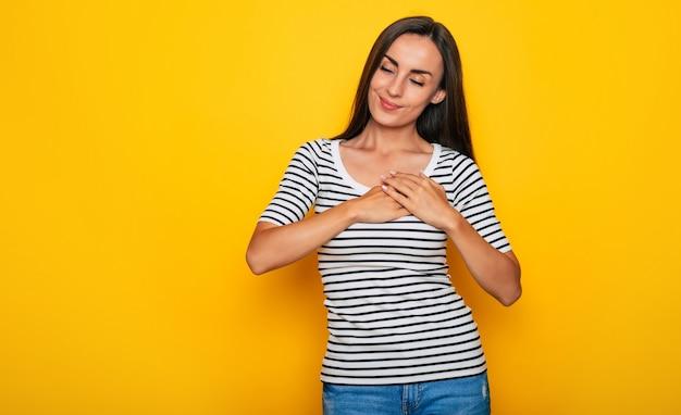 Śliczna delikatna młoda kobieta w zwykłych ubraniach trzyma ręce na piersi z zamkniętymi oczami