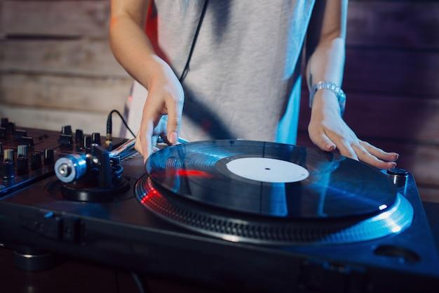 Śliczna dj kobieta ma zabawę bawić się muzykę przy klubu przyjęciem