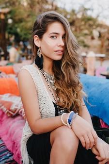 Śliczna długowłosa dziewczyna w modnych bransoletkach i kolczykach pozuje na zewnątrz, odpoczywając na imprezie w parku
