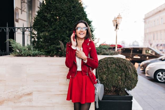 Śliczna długowłosa kobieta rozmawia przez telefon z szarej torebki