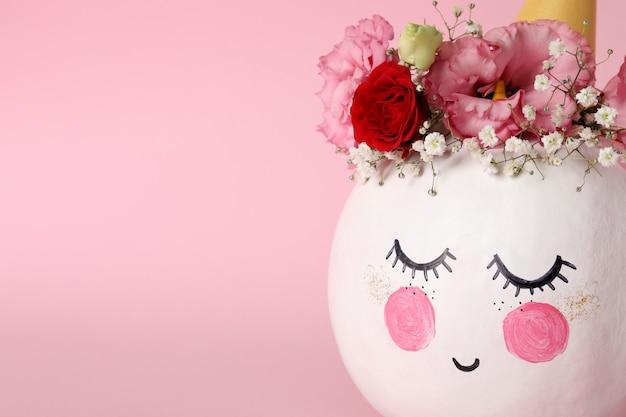 Śliczna dynia z halloweenowym makijażem na różowym tle