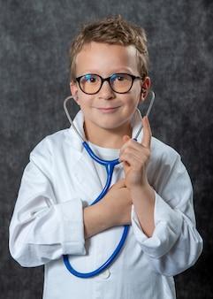 Śliczna dzieciak chłopiec odzieży medyczny mundur bawić się lekarkę, portret