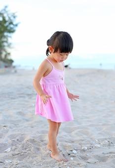 Śliczna dziecko dziewczyny pozycja na piasek plaży