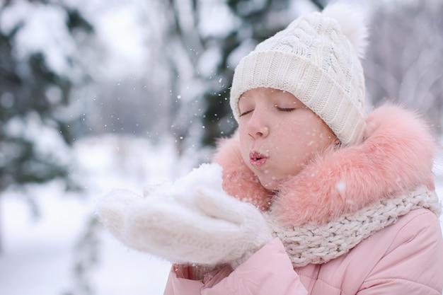 Śliczna dziewczyna bawi się śniegiem w parku na ferie zimowe