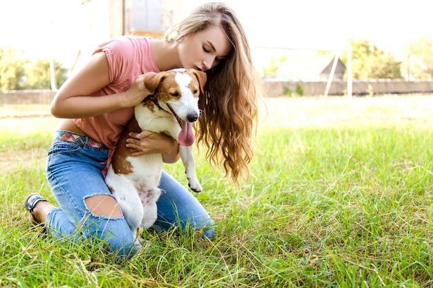 Śliczna dziewczyna bawi się z psem w parku