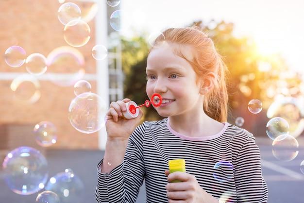 Śliczna dziewczyna bawić się z mydlanymi bąblami