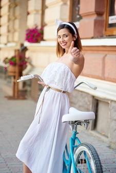 Śliczna dziewczyna blisko retro rowerowych przedstawień klasy, stary miasto