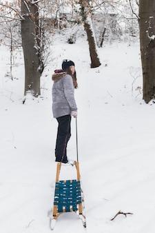 Śliczna dziewczyna ciągnie pustego saneczki na śnieżnym krajobrazie w zimie