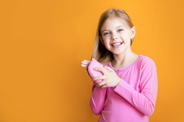 Śliczna dziewczyna czesze jej miękkie włosy na pomarańczowej ścianie