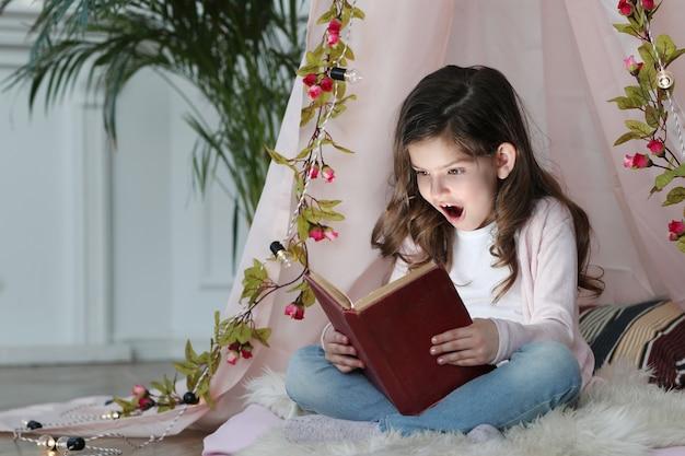 Śliczna dziewczyna czytająca książkę wokół uroczej dekoracji